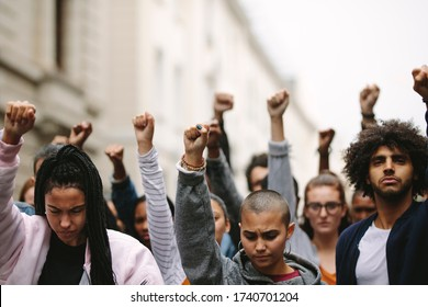 Group of protesters on the road with their arms raised. Multi-ethnic people protesting on the street.