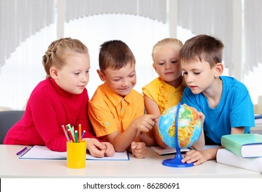 Group of pupils studying a globe together