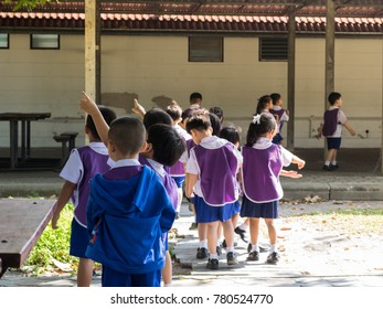 group of purple kids pointing to the tree and walking around the school learning about world