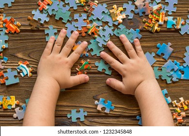a group of puzzles, child's hands on a wooden table background. puzzle game, preschool education.