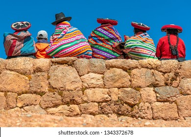 A group of Quechua indigenous women in traditional clothing and a young boy sitting and chatting on an ancient Inca wall in the archaeological site of Chinchero in the region of Cusco city, Peru.