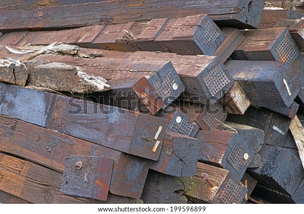 A group of railroad ties covered in creosote.