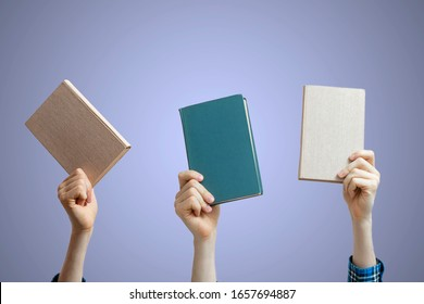 group of raised people hands holding books isolated against the colorful background, share knowledge and study
