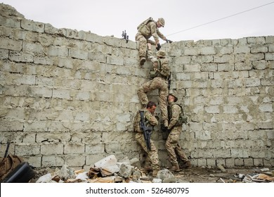 Group of rangers team climbing from a wall