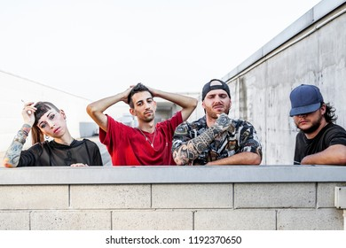 group of rappers posing leaning against the wall on the metal rooftops of an abandoned building