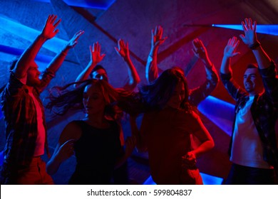 Group of raving dancers enjoying discotheque