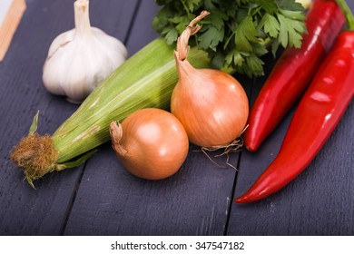 Group of raw domestic vegetarian ingredients vegetables garlic yellow onions corncob red chili peppers juicy parsley piquant condiments for healthy food studio on dark wooden background, horizontal