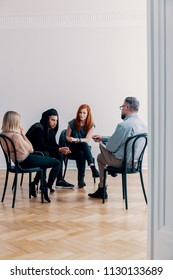 Group of rebellious teenagers talking to a psychologist in a rehab facility