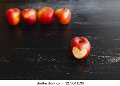 group of red apples with different tones on dark wooden table, healthy food concept with copyspace to add your text
