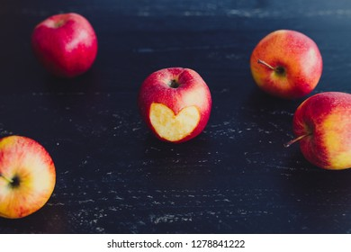 group of red apples with different tones on dark wooden table, healthy food concept