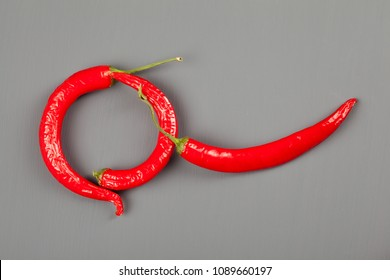 Group of red chili peppers on gray background