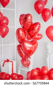 Group of red heart balloons in a white interior. Valentine's Day