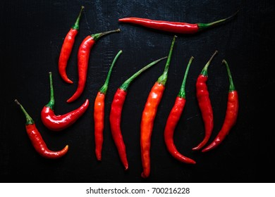 Group Red hot chili pepper on black background grunge textures old wood, top view and trending flat lay design.