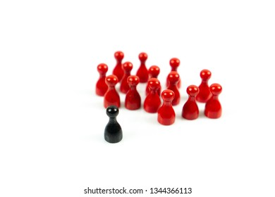 A group of red meeple are facing a black meeple, white background and copy space