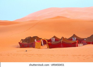 Group of red nomad tents around courtyard, Berber camp in Sahara desert, Morocco