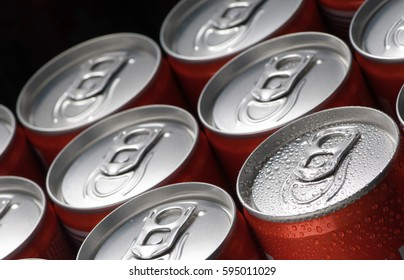 a group of red tin cans with water droplets close-up on a black background