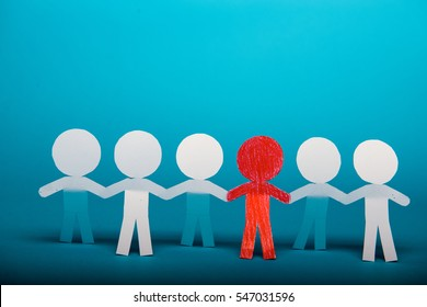 A group of red and white paper people holding hands indicating community support, partnership and togetherness.