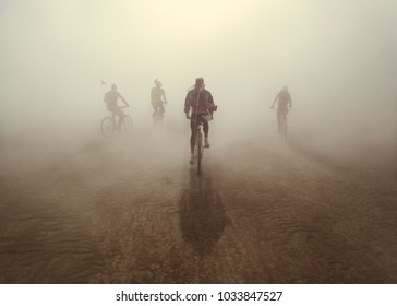 group riding bicycles into hazy dusty sunset