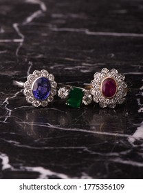 a group of rings on a marble table. Close up detail shows a sapphire, a ruby, and an emerald gemstone. Jeweler, Jewellry, jewels, gemstones. wedding rings or engagement rings. antique and elegant