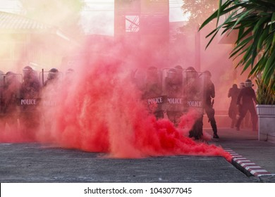 Group riot police with protective gear and shields surrounded by tear gas and pink color smoke bomb in tactical training