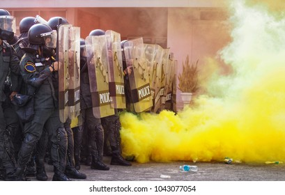 Group riot police with protective gear and shields surrounded by tear gas and yellow color smoke bomb in tactical training