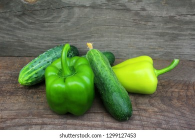 Group Ripe Green pepper and cucumber lying on a wooden background. Close up view from top.