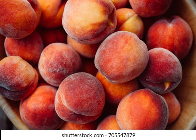 A group of ripe peaches in a bowl
