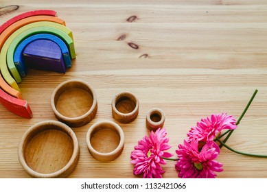 Group of round and empty wooden bowls and purple flowers with free space for text with montessori wood rainbows.