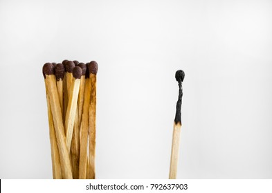 a group of row of matches pulled away from one burnt.  Racism, bullying, social exclusion, depression and loneliness concept.