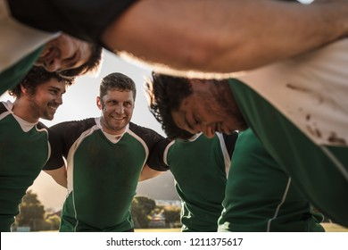 Group of rugby players standing in circle. Professional rugby players in huddle during the game.