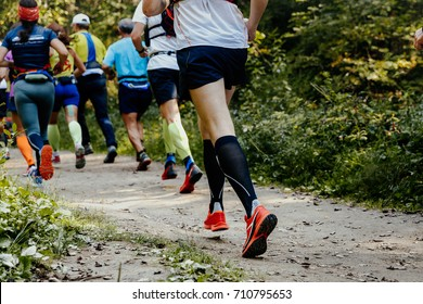 group of runners athletes running in forest trail marathon