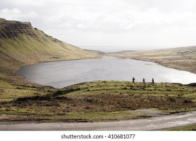 Group of runners in training around a Loch on the Isle of Skye, Scotland
