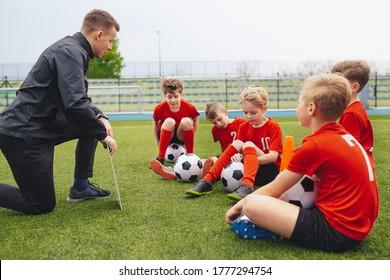 Gruppe trauriger Jungen mit Trainer nach dem Verlust des Fußballturniers. Kinder, die Junior-Schule Fußball-Trainer. Trainer erklärt Spieltaktik mit Whiteboard