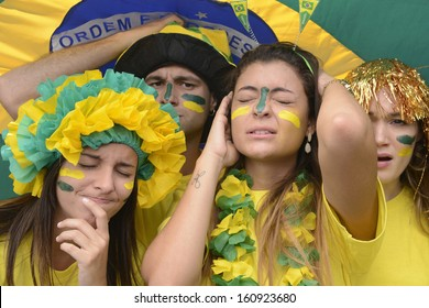 Group of sad crying brazilian soccer fans disappointed with team defeat.