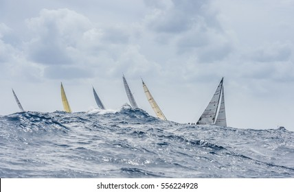 The group of sailing boats with big wave. We can see only sails.