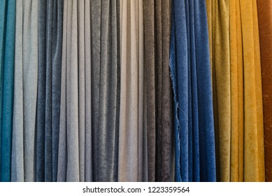Group of sample various colour fabric and textile dangle and hang vertically from above cover entire background.