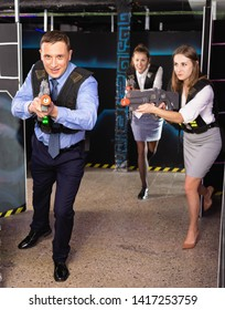 Group of satisfied positive   colleagues holding laser pistols playing laser tag game