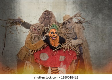 A group of scarecrows and a human squash behind a flame wall