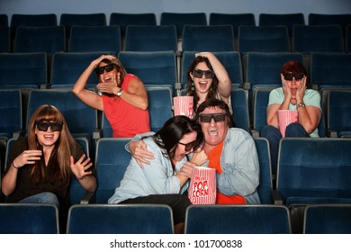 Group of scared people with 3d glasses screaming in a theater