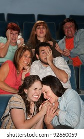 Group of scared people watch horror movie in theater