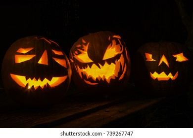 Group of scary candle lit Halloween pumpkins isolated on a black background.