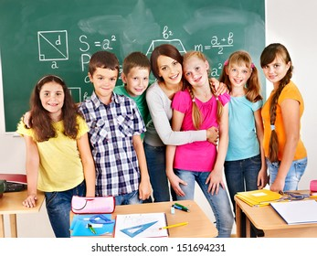 Group of school child sitting on desk in classroom.