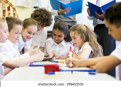A group of school children can be seen working on digital tablets and whiteboards, they are all working happily. Two unrecognizable teachers can be seen in the background.
