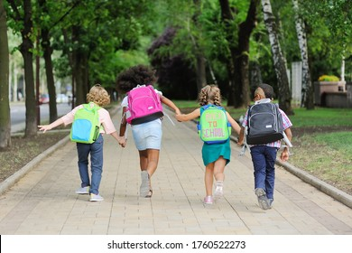 a group of school children of different races in colorful clothes with school bags and backpacks run to school against the background of green m Park. Back to school, knowledge day, education - Shutterstock ID 1760522273