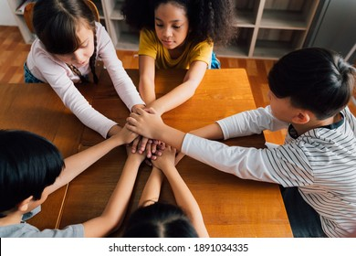 Group of school friends with hands stacked one on top of another, friendship, support, togetherness. Multiethnic school children with hands touching on top of each other