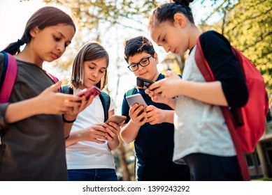 Group of school kids hang out in schoolyard and using smart phone