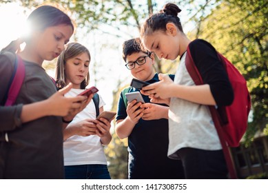 Group of school kids hang out on the street and using smart phone