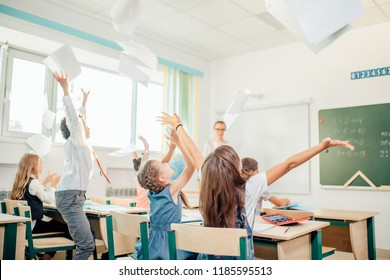 Group of school kids have fun in class and throwing paper in air