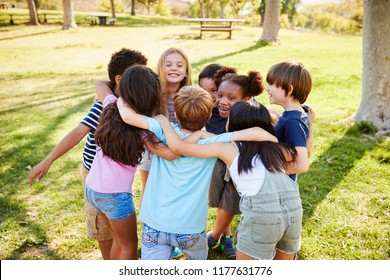 A group of school kids in a huddle outdoors, back view