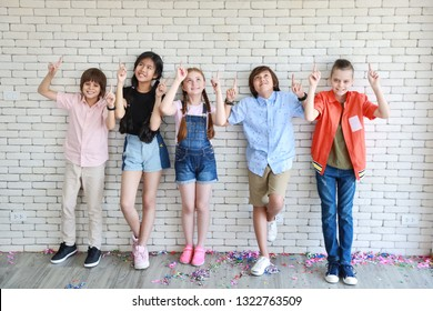 group of school kids pointing something in the top in classroom with white wall (education concept)
